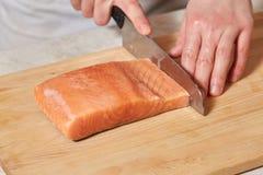 Chef making sushi rolls. Cutting salmon fish on wooden board. Chef making sushi rolls. Hands cutting salmon fish on wooden board Stock Photo