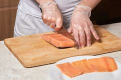 Chef making sushi rolls. Cutting salmon fish on wooden board. Chef making sushi rolls. Hands cutting salmon fish on wooden board Stock Image