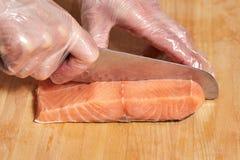 Chef making sushi rolls. Cutting salmon fish on wooden board. Chef making sushi rolls. Hands cutting salmon fish on wooden board Royalty Free Stock Image