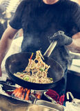 Chef making tasty noodles in a wok. Royalty Free Stock Photos