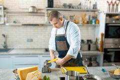 Chef is making thin dough with special machine, toned image Royalty Free Stock Photo