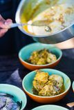 Cooking class. Chef making traditional Sri Lankan chicken curry dish at cooking class Stock Images