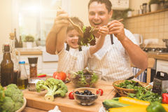 Chef man cooking on the kitchen with little son. Royalty Free Stock Photos