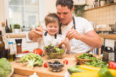 Chef man cooking on the kitchen with little son. Chef men cooking salad on the kitchen with little son. Paranting concept royalty free stock photography