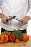 Chef - man sharpening knife. Professional chef sharpening knife inlcluding assorted fresh vegetables stock images