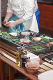 chef man in uniform frying a meat beefsteak slice on grill Stock Photo