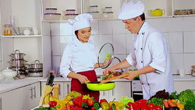Chef man and woman professional in hat cooking vagetable . Used tripot stock video footage
