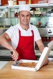 Chef masculin à l'aide du coupeur de pizza photo stock