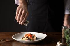 Chef masculin dans l'uniforme ajoutant des épices au plat savoureux Photo libre de droits