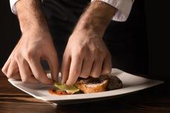Chef masculin dans l'uniforme préparant le plat savoureux sur la table Image libre de droits