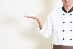Chef masculin indien dans l'uniforme tenant un plat vide Photos libres de droits