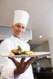 Chef masculin sûr avec des aliment cuits dans la cuisine images stock