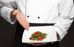 Chef masculin tenant le plat avec le plat savoureux Photo stock
