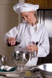 Chef measuring. Uniformed female Chef pouring vanilla extract liquid into a measuring spoon Royalty Free Stock Image