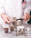 Chef Measuring Salt. Assertive portrait comp of a uniformed Chef leveling a spoonful of salt over a cold marble board Royalty Free Stock Photos