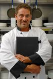 Chef with menu. A smiling chef holds a menu in a restaurant kitchen Royalty Free Stock Photography