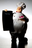 Chef with menu board. A plump character chef figure wearing a white apron and hat holds a blank menu board stock image