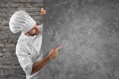 Chef menu. Chef showing and indicates his menu on a grey billboard royalty free stock photography
