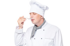 Chef with a metal spoon tastes the soup Royalty Free Stock Images