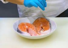 Chef mettant le sel sur la tranche saumonée, cultivée des mains faisant cuire les poissons saumonés photos stock