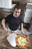 Chef mit frischem nehmen Pizza heraus Lizenzfreies Stockbild