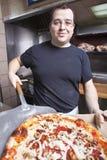 Chef mit frischem nehmen Pizza heraus Lizenzfreie Stockfotografie