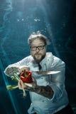 Chef mit Gemüse und Koch ` s kinfe, das unter Wasser aufwirft Stockfotografie