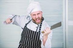 Chef mit Messern Fachmann in der K?che r ver?rgerter b?rtiger Mann mit Messer m?gen Sie Nahrung essen ?berzeugt lizenzfreie stockfotografie