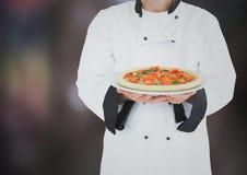 Chef mit Pizza gegen undeutlichen dunkelgrauen Hintergrund Lizenzfreies Stockbild