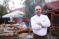 Chef mit Restaurant und gebratenem Karkassenhintergrund lizenzfreie stockfotos