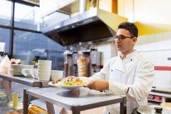 Chef mit Teller auf Platte am Kebabshop Stockfoto