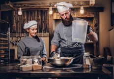 Chef mixes the ingredients for the dough. Chef teaching his assistant to bake bread in the bakery. Chef mixes the ingredients for the dough. Chef teaching his royalty free stock photography