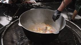 Chef mixes seafood and vegetables soup in a large cauldron on the street, close-up. Slow motion.