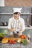 Chef with mortar. An Asian woman chef smiling cooking with Thai mortar in the kitchen Royalty Free Stock Photography