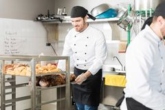 Chef With Mouthwatering Pastries In Bakery. Male baker arranging tray of fresh pastries on rack in bakery kitchen royalty free stock image