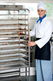 Chef moving tray rack towards corner Stock Photography