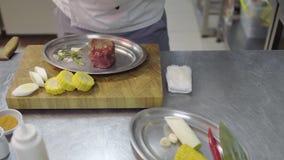 Chef non reconnu dans le tablier versant le morceau de viande cru avec l'assaisonnement avant la cuisson dans le four dans la cui banque de vidéos
