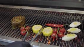 Chef non reconnu faisant cuire le légume sur le gril dans le plan rapproché de cuisine de restaurant Viande, maïs, tomates-cerise banque de vidéos