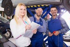 Chef och besättning som gör upp kontrollen av den brutna bilen royaltyfri fotografi