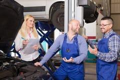 Chef och besättning som gör upp kontrollen av den brutna bilen Royaltyfri Foto