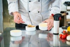 Chef oder Patissier, die eine Creme brulee zubereiten Stockfotos