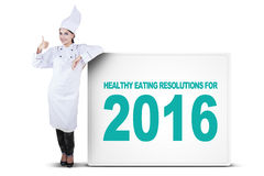 Chef with OK sign and healthy eating resolutions. Image of female chef showing thumb up while standing near a billboard with a text of healthy eating resolutions Royalty Free Stock Image