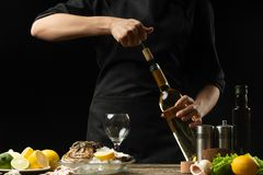 Chef opens Italian dry wine with oysters with lemon, on a dark background.  royalty free stock photography
