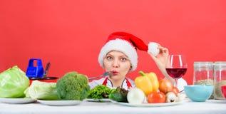 Chef ou femme au foyer de femme faisant cuire tandis que chapeau de Santa d'usage Les meilleures recettes de Noël Idée de dîner d photos stock