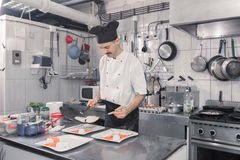Chef pan finishing meals plates eggs. One young adult man, chef pan finishing meals plates eggs, commercial kitchen professional stock photos