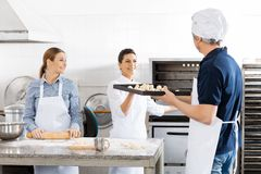 Chef Passing Baking Sheet To Colleague By Oven Stock Photography