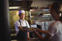 Chef passing tray with french fries to waitress. In the commercial kitchen Stock Photo