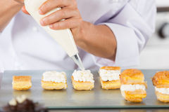 Chef with a pastry bag. Chef decorating with a pastry bag with cream Stock Image