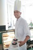 Chef pastry in pose. Next by cake display Royalty Free Stock Photography
