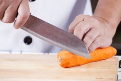 Chef is peeling carrots Stock Images